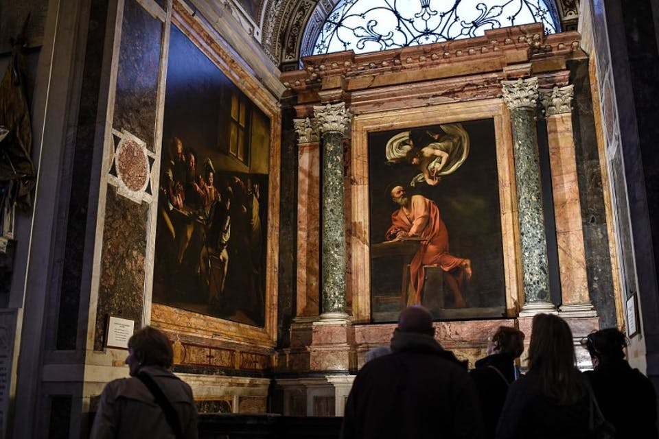 "Visitors look at a painting by Italian artist Caravaggio ""The Inspiration of Saint Matthew"" (R) in the Contarelli Chapel in the Church of St. Louis of the French (San Luigi dei Francesi), on November 28, 2015 in Rome. AFP PHOTO / ANDREAS SOLARO / AFP / ANDREAS SOLARO (Photo credit should read ANDREAS SOLARO/AFP/Getty Images)"