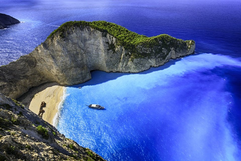 Famous Navagio beach (Smugglers Cove) with abandoned smuggler ship. Zakynthos island, Greece. ProPhoto RGB color space.